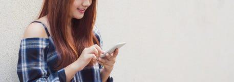 使用在灰色背景的愉快的美丽的亚裔妇女一个智能手机 葡萄酒作用样式图片 全景的横幅 免版税库存照片
