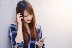 使用在灰色背景的愉快的美丽的亚裔妇女一个智能手机 葡萄酒作用样式图片 库存照片