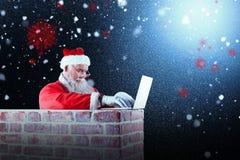 使用在烟囱的圣诞老人的综合图象膝上型计算机 图库摄影
