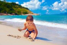 使用在热带海岛海滩的沙子的微笑的孩子 库存图片