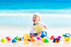 使用在热带海滩的婴孩开掘在沙子 免版税库存照片
