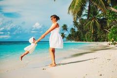 使用在热带海滩的母亲和daugher 免版税库存图片