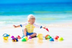 使用在热带海滩的婴孩开掘在沙子 库存图片