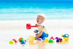 使用在热带海滩的婴孩开掘在沙子 库存照片