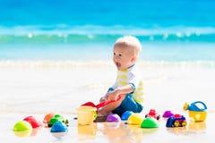 使用在热带海滩的婴孩开掘在沙子 免版税库存图片
