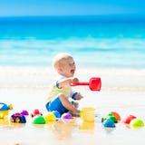 使用在热带海滩的婴孩开掘在沙子 图库摄影