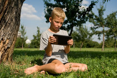 使用在片剂个人计算机的男孩 免版税库存照片
