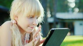 使用在片剂的一个六岁的女孩的画象 在草的谎言在房子附近 股票视频