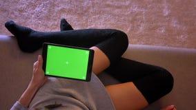 使用在片剂的女性秀丽博客作者特写镜头画象社会媒介有绿色屏幕的 在舒适的女孩腿 股票视频