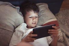 使用在片剂的小男孩在黑暗的卧室 库存图片