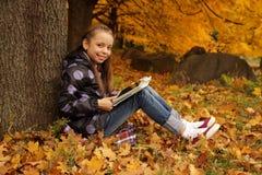 使用在片剂的微笑的女孩在公园 免版税库存照片