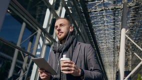 使用在片剂计算机上的白种人商人企业应用程序,走在城市在一运作的午休时间期间 英俊 影视素材