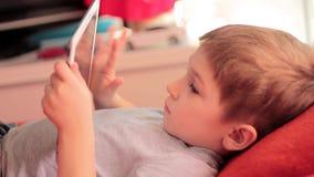 使用在片剂计算机游戏的小男孩 股票录像