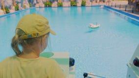 使用在玩具小船乘驾控制的女孩,在水池漂浮 股票录像