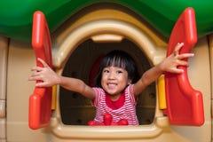使用在玩具房子里的亚裔中国小女孩 免版税库存照片
