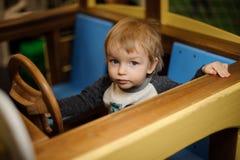 使用在玩具木汽车的逗人喜爱的小男孩 免版税库存图片
