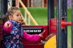 使用在玩具汽车的女孩在公园 库存照片