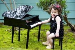 使用在玩具钢琴的小女孩 免版税图库摄影
