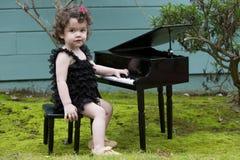 使用在玩具钢琴的小女孩 库存图片