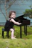 使用在玩具钢琴的小女孩 免版税库存照片