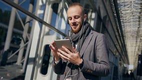 使用在现代商业中心附近的片剂计算机英俊的商人画象  年轻有胡子的人卷动 股票视频