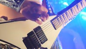 使用在电吉他的无法认出的人在阶段在音乐会期间 关闭吉他弹奏者的手指在串 股票视频