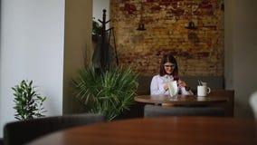 使用在电话饮用的咖啡的智能手机女孩app微笑在咖啡馆 美丽的多文化年轻偶然女性 股票录像