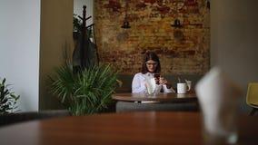 使用在电话饮用的咖啡的智能手机女孩app微笑在咖啡馆 美丽的多文化年轻偶然女性 影视素材