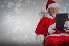 使用在白色背景的圣诞老人的综合图象数字式片剂 库存照片