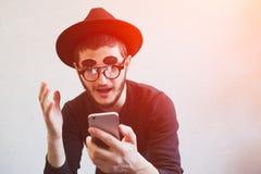 使用在白色背景的智能手机情感人画象,穿戴在黑色 佩带的太阳镜和帽子 图库摄影