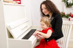 使用在白色钢琴的母亲和女儿 免版税库存照片