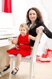 使用在白色钢琴的母亲和女儿 库存照片