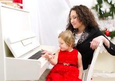使用在白色钢琴的母亲和女儿 免版税图库摄影