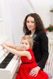 使用在白色钢琴的母亲和女儿 免版税库存图片