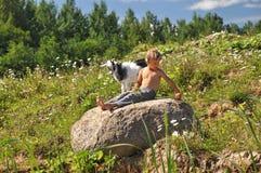 使用在石头的男孩和山羊 免版税图库摄影