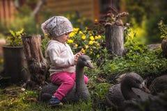 使用在神仙的开花的庭院里的逗人喜爱的女婴在有鹅的乡下在美丽的花中在象征happ的夏日 图库摄影