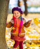 使用在秋天公园的愉快的小女孩 库存照片