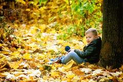 使用在秋天公园的美丽的滑稽的男孩 免版税库存照片