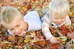 使用在秋天叶子堆的两个幼儿 免版税库存图片