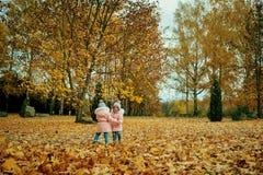 使用在秋天的两个愉快的孩子在公园穿衣 免版税库存照片