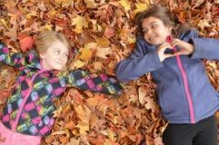 使用在秋天的叶子的女孩 免版税库存照片