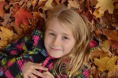 使用在秋天的叶子的小女孩 免版税库存照片