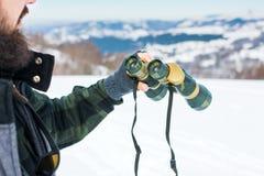 使用在积雪的山的人双筒望远镜 图库摄影