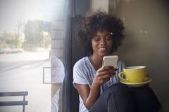 使用在窗口旁边的年轻黑人妇女智能手机在咖啡馆 免版税库存照片