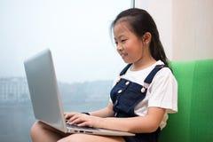 使用在窗台的亚裔中国小女孩膝上型计算机 库存照片