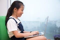 使用在窗台的亚裔中国小女孩膝上型计算机 免版税库存照片