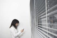 使用在窗帘前面的女实业家手机 免版税库存图片