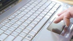 使用在笔记本键盘的人触感衰减器有他的有蓝色轻的色彩的手指的 股票录像