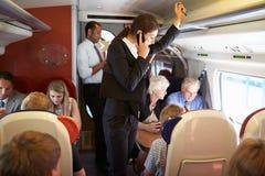 使用在繁忙的市郊火车的女实业家手机 免版税库存照片