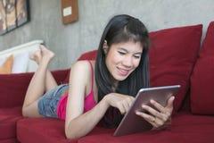 使用在红色沙发的年轻美丽的妇女计算机片剂 免版税库存图片